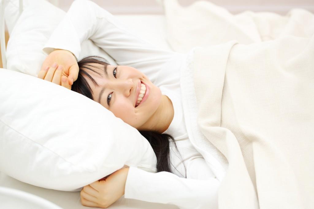 あたたかそうな寝具で笑顔の女性