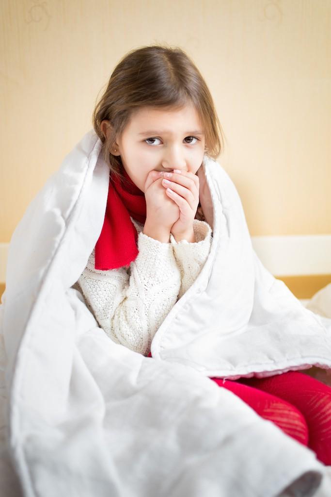 寒そうに毛布にくるまる女性
